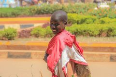 Um menino local anda abaixo da rua de Kampala, gerencie ao redor e sorri fotografia de stock