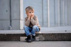 Um menino louro branco com quatro anos em um fundo concreto cinzento que senta-se sobre nas etapas, pensativas fotos de stock