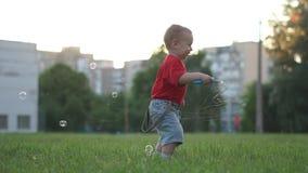 Um menino louro pequeno salta e felizmente acenando sua varinha com bolhas de sabão vídeos de arquivo