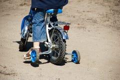 Um menino monta em uma bicicleta Fotos de Stock Royalty Free