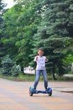 Um menino monta o gyroscooter Imagens de Stock Royalty Free