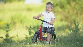 Um menino monta uma bicicleta sem pedais video estoque