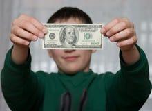 Um menino mostra 100 dólares Imagens de Stock