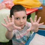 Um menino mostra as mãos Imagem de Stock Royalty Free