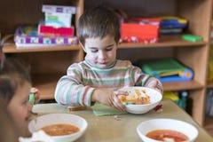 Um menino na idade de 5 anos que come a sopa no jardim de infância Imagem de Stock Royalty Free