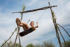 Um menino na praia em um balanço Dia ensolarado do verão foto de stock royalty free