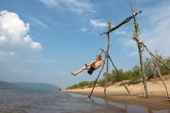 Um menino na praia que balan?a em um balan?o Dia ensolarado do ver?o fotos de stock