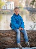 Um menino na roupa azul senta-se em uma árvore em um parque fotografia de stock royalty free