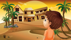 Um menino no deserto que está na frente das casas de madeira Foto de Stock Royalty Free