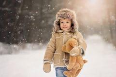 Um menino no inverno branco, nevado na floresta fotografia de stock