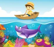Um menino no oceano com um tubarão Fotos de Stock Royalty Free