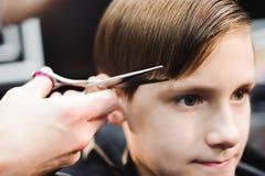 Um menino novo bonito que obtém um corte de cabelo imagens de stock royalty free