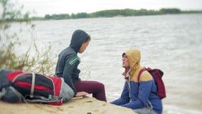 Um menino novo com seu pai e um turista backpack na praia vídeos de arquivo