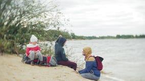 Um menino novo com seu pai e um turista backpack na praia video estoque
