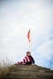 Um menino novo com uma bandeira americana, alegria de ser um americano imagens de stock
