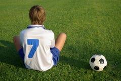 Um menino novo com uma esfera de futebol Fotos de Stock
