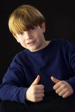 Um menino novo dá a aprovação fotos de stock