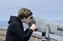 Um menino novo em Brasstown calvo olhando a vista com um telesco Imagens de Stock Royalty Free