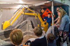 Um menino novo opera uma máquina escavadora diminuta imagens de stock