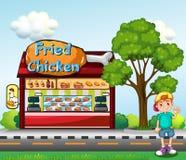 Um menino novo perto da loja do frango frito Fotos de Stock