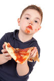 Um menino novo que come a pizza Imagem de Stock Royalty Free