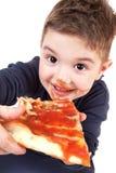 Um menino novo que come a pizza Fotos de Stock Royalty Free