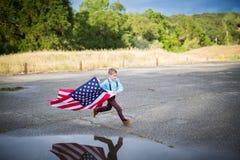 Um menino novo que corre com a bandeira americana que mostra o patriotismo para seu próprio país, une estados imagem de stock