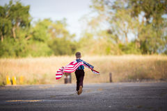 Um menino novo que corre com uma bandeira americana, alegria de ser um americano imagens de stock
