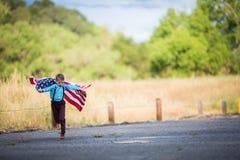 Um menino novo que corre com uma grande bandeira americana que mostra o patriotismo para seu próprio país, une estados foto de stock