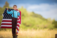 Um menino novo que guarda com a bandeira americana que mostra o patriotismo para seu próprio país, une estados fotos de stock royalty free