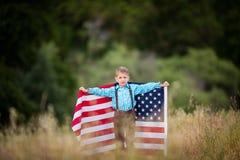 Um menino novo que guarda uma grande bandeira americana, alegria de ser um americano imagens de stock