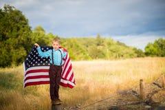 Um menino novo que guarda uma grande bandeira americana que mostra o patriotismo para seu próprio país, une estados imagens de stock