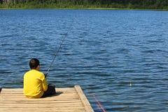 Um menino novo que senta-se em uma doca e em uma pesca Fotos de Stock Royalty Free