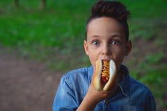 Um menino novo toma uma mordida de um cachorro quente foto de stock royalty free