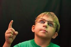 Um menino ocasional com vidros aumentou seu dedo acima e olha acima, contra um fundo escuro foto de stock