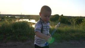 Um menino pequeno alegre que acena uma varinha da bolha no campo no movimento lento filme