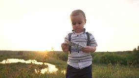 Um menino pequeno bonito olha com interesse em cédulas de cem dólares, movimento lento video estoque