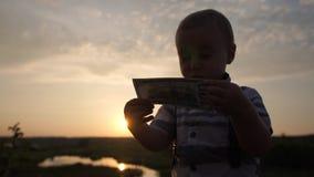 Um menino pequeno bonito olha com interesse em cem notas de dólar no movimento lento video estoque
