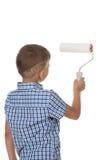 Um menino pequeno do construtor na camisa quadriculado azul, pintando a parede com o rolo de pintura, isolado no fundo branco Fotos de Stock Royalty Free