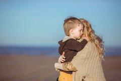 Um menino pequeno está abraçando com seu mum Imagem de Stock