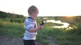 Um menino pequeno guarda um brinquedo pequeno do cavalo, corre felizmente com ele na estrada no por do sol filme