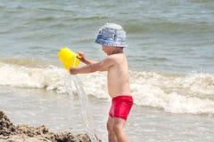 Um menino pequeno no litoral derrama a água de uma cubeta na perspectiva do mar e das ondas, fotografia de stock royalty free