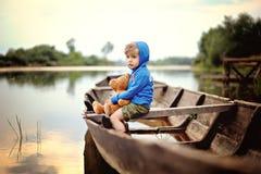 Um menino pequeno, pensativo em uma camiseta encapuçado azul senta-se em bota arborizada com o urso de peluche no rio foto de stock royalty free
