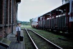 Um menino pequeno, pensativo que veste no estilo retro, esperando imagens de stock