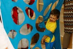 um menino pequeno pisa sobre, escaladas, trilhos, passagens em um furo, um corte, uma abertura em uma tela azul, na matéria Jogo  fotos de stock
