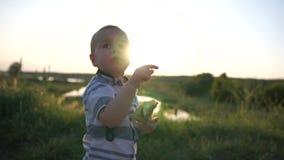 Um menino pequeno que come uma torta na natureza e que mostra algo no céu vídeos de arquivo
