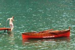 Um menino pisa fora da doca vermelha em um mar verde, trações vermelhas do barco de fileira próximo ilustração stock