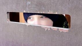 Um menino preteen com os olhos bonitos que espiam através de um furo grande na parede de madeira Emo??o humana, express?o facial video estoque