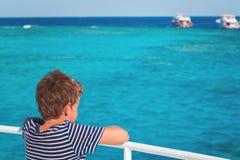 Um menino que aprecia uma viagem do mar do barco imagem de stock royalty free