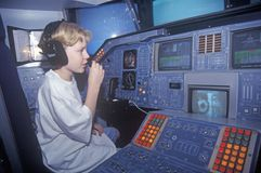 Um menino que atende ao acampamento do espaço no George C Marshall Space Flight Center em Huntsville, Alabama, senta-se na cabina foto de stock